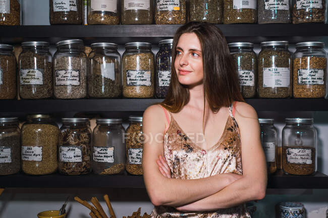 Woman with arms crossed in spice shop — Stock Photo