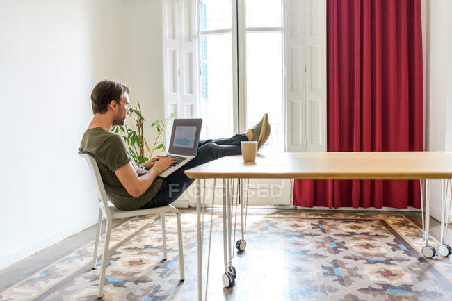 Young man sitting in office with laptop — Stock Photo
