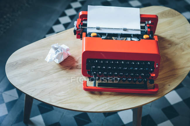 Close-up red typewriter on small table with paper sheet inserted — Stock Photo