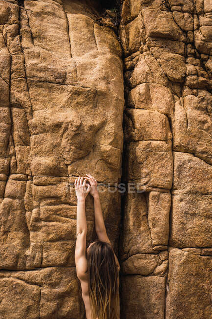 Back view of naked woman climbing up on rough mountain wall. — Stock Photo