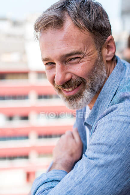 Retrato de hombre barbudo con arrugas sonriendo y mirando a la cámara sobre fondo borroso del edificio - foto de stock