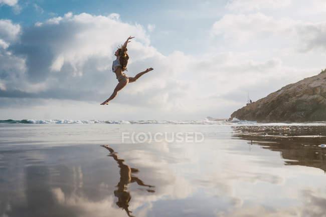 Ragazza che salta sulla spiaggia con cielo nuvoloso sullo sfondo — Foto stock