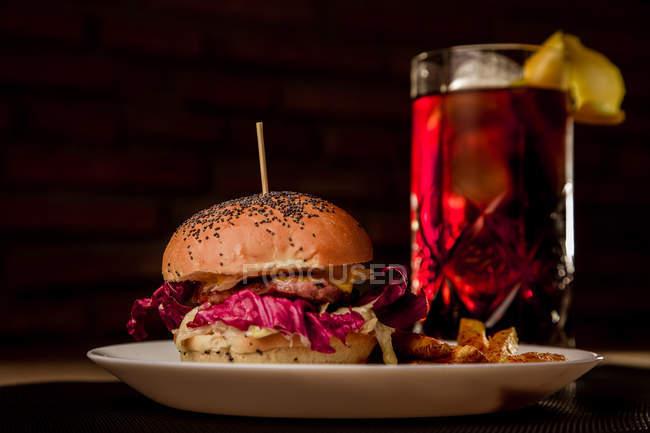 Sabrosa hamburguesa con papas fritas en plato y vaso de coque - foto de stock