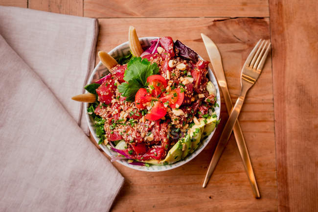 Bowl of tasty vegetable salad with avocado on wooden table — Stock Photo