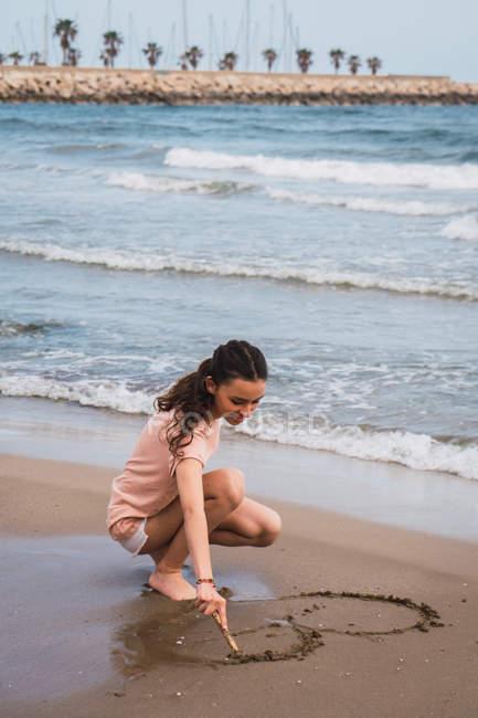 Teen ragazza accovacciata e pittura con bastone sulla sabbia in riva al mare — Foto stock