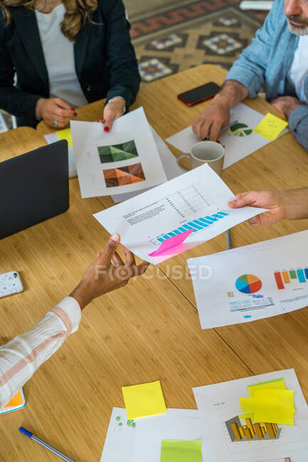 Crop view from above of group of workers sitting at meeting table and discussing scheme and diagrams in office — Stock Photo