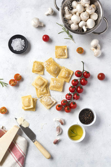 Uncooked ravioli and spices with tomatoes and mushrooms on table — Stock Photo