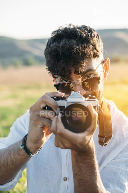 Красивый молодой парень в солнечных очках весело улыбается и держит ретро фотокамеру, стоя на размытом фоне удивительной сельской местности — стоковое фото
