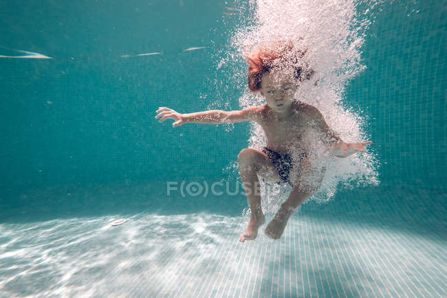 Boy in swimming trunks diving into transparent blue pool water — Stock Photo