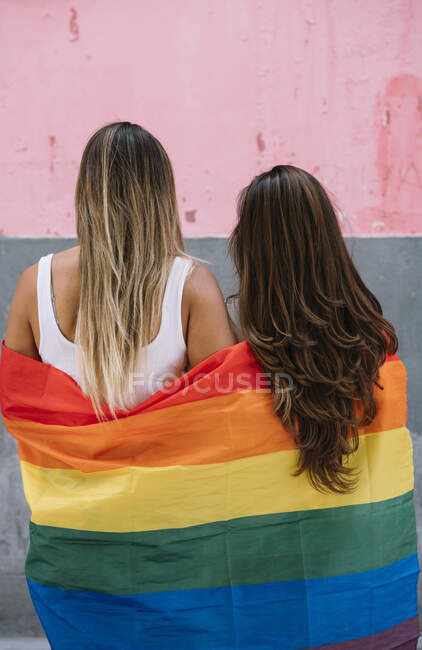 Пара лесбиянок с флагом гей-гордости на улице Мадрида — стоковое фото