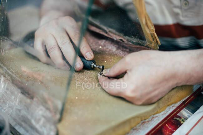 Руки нерозпізнаного майстра роблять гравірування на тарілці. — стокове фото