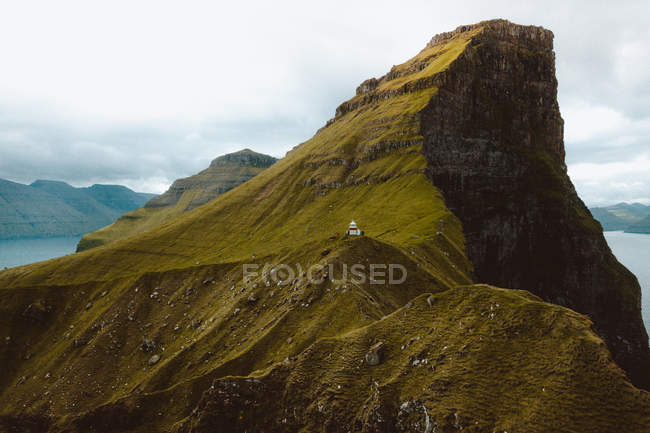 Pequena casa na falésia rochosa verde sob um céu nublado nas Ilhas Feroe — Fotografia de Stock