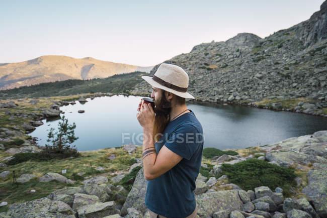 Jovem de chapéu em pé perto do lago nas montanhas com copo — Fotografia de Stock