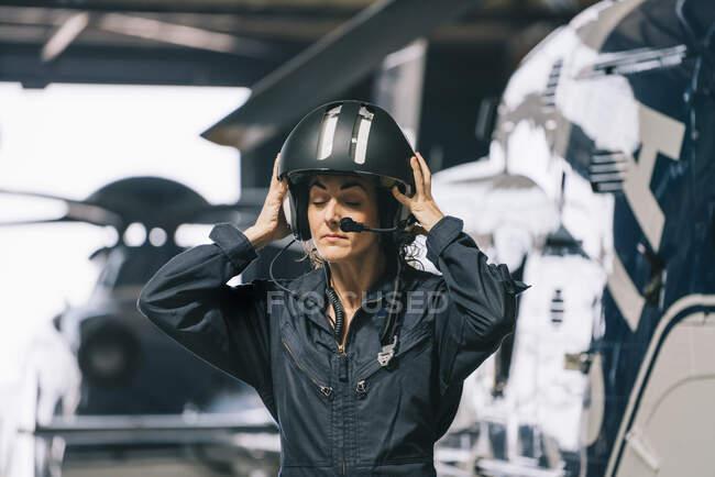 Девушка-пилот позирует с вертолетом и шлемом — стоковое фото