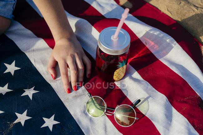 Colpo nel grano di donna seduta con drink e occhiali da sole sulla bandiera americana alla luce del sole. — Foto stock