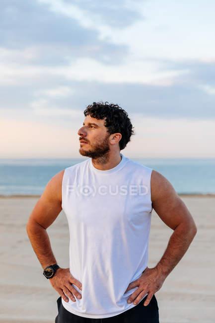 Homem positivo em sportswear com as mãos na cintura, enquanto em pé na praia de areia durante o pôr do sol — Fotografia de Stock