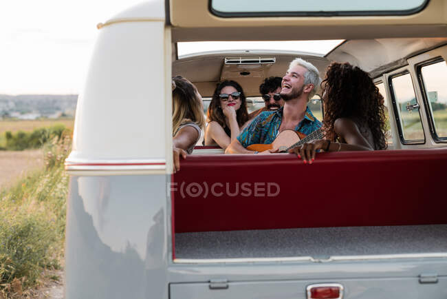 Group of young people laughing and listening to handsome guy playing acoustic guitar inside vintage van in nature — Stock Photo