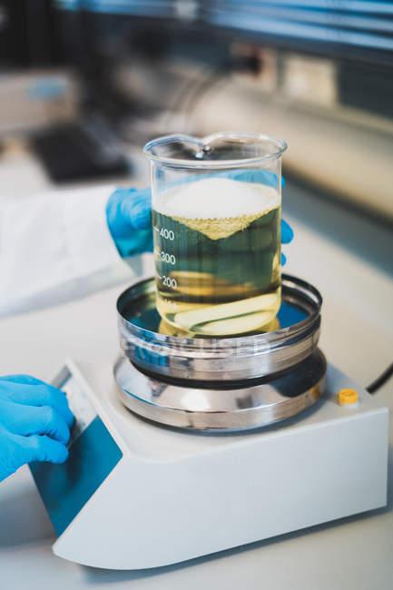 Руки особі в синій медичні рукавички поклавши дозування Кубок з жовтувата рідина накипу в лабораторії — стокове фото
