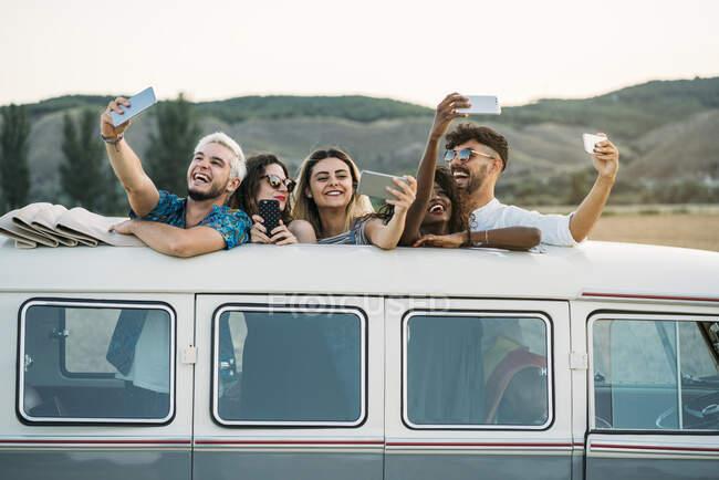 Grupo de pessoas diversas alegres que estão dentro da van vintage com telhado aberto e posando para selfie enquanto viajam no campo juntos — Fotografia de Stock