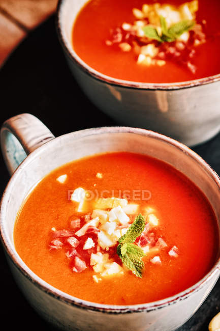 Tomato gazpacho served with egg and ham in cups — Stock Photo