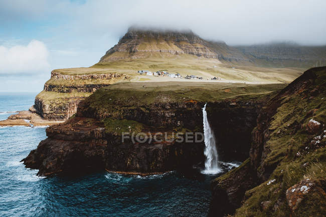 Picturesque view of coastal cliffs and spraying waterfall on Feroe Islands — Stock Photo