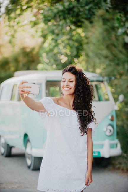 Cheerful woman taking selfie near bright retro van — Stock Photo