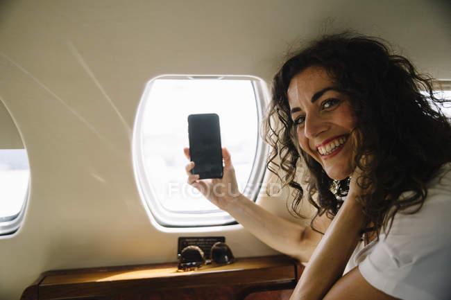 Cuadro de toma de la mujer a través de la ventana de avión - foto de stock