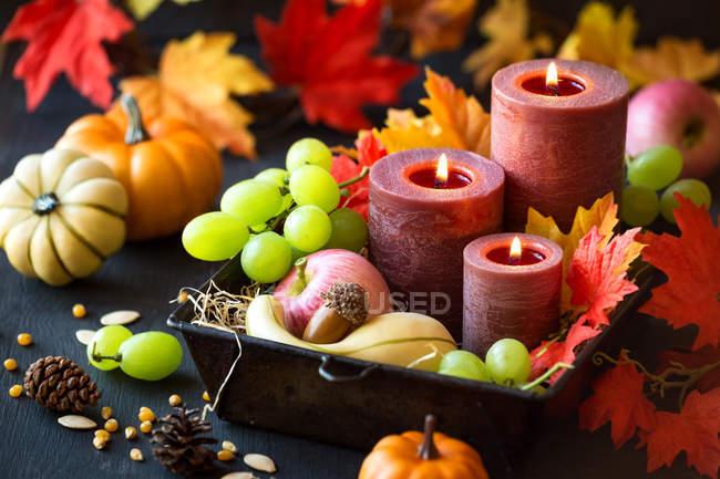 Водоспад до Дня подяки зі свічками, осіннім листям, виноградом, гарбузами, насінням кукурудзи та шишками сосни. — стокове фото