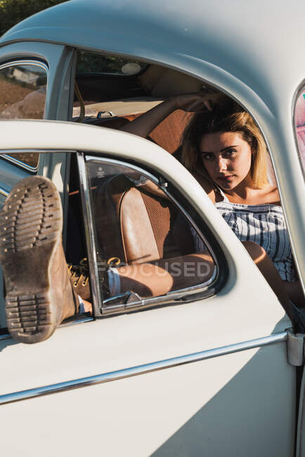 Sleeping woman leaning legs on opened door of retro car and sleeping on seat in sunlight — Stock Photo
