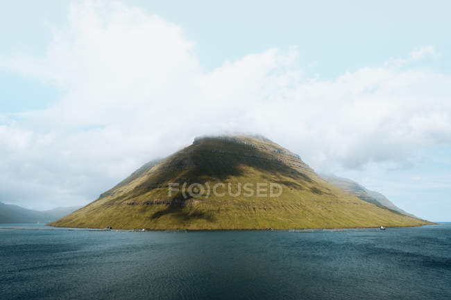 Picturesque view to calm blue ocean and small green island, Feroe Islands — Stock Photo