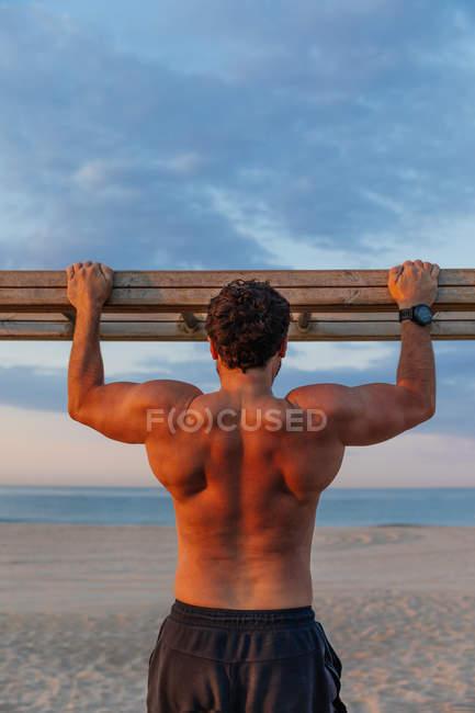 Barbudo hombre sin camisa escalando escalera de madera mientras hace ejercicio en la playa - foto de stock