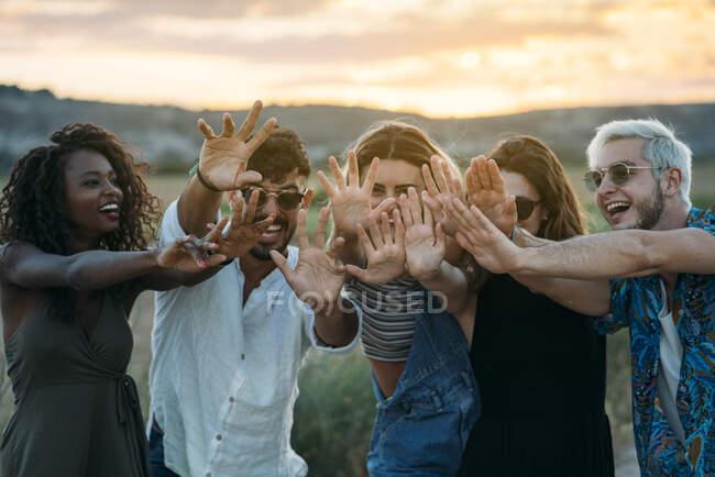 Grupo de diversos jóvenes amigos sonriendo y extendiendo las manos hacia la cámara mientras están de pie sobre un fondo borroso de un paisaje increíble durante la puesta del sol — Stock Photo