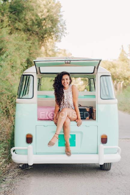 Cheerful brunette sitting in bright retro van — Stock Photo
