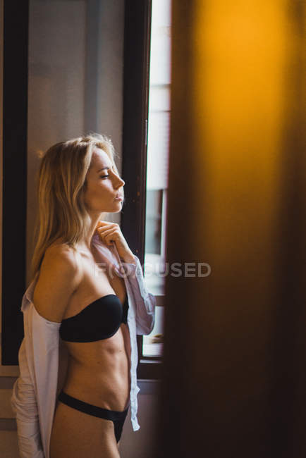 Attractive sensual young woman in lingerie standing at window — Stock Photo