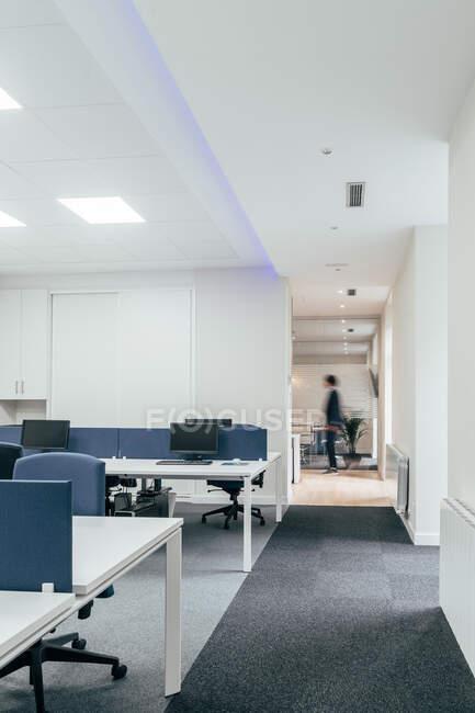 Vista da pessoa anônima em pé na elegante área de escritório durante o dia útil — Fotografia de Stock