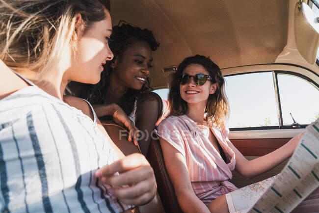 Вид сбоку веселых подруг, читающих карту, сидя в ретро-машине и счастливо путешествуя вместе — стоковое фото