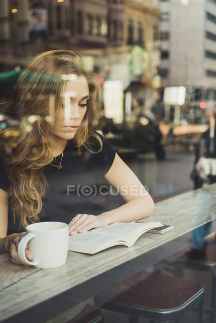 Молодая женщина сидит с книгой и кофе у окна в кафе — стоковое фото