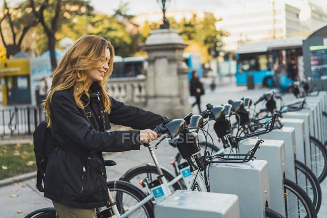 Frau nehmen Fahrrad im Stadtpark — Stockfoto