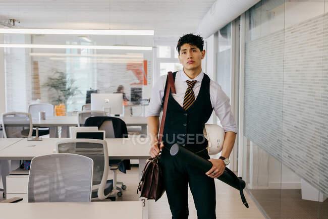 Молодий чоловік з кресленням на роботі. — стокове фото