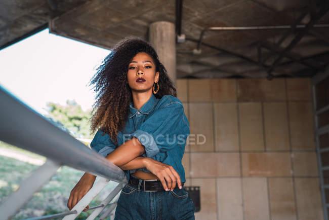 Giovane donna attraente con i capelli ricci in abiti di jeans in piedi sul balcone vicino ringhiera e guardando la fotocamera — Foto stock