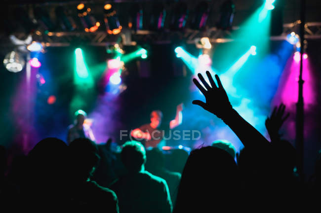 Silhouettes of unrecognizable people holding hands up and having fun during amazing music performance — Stock Photo