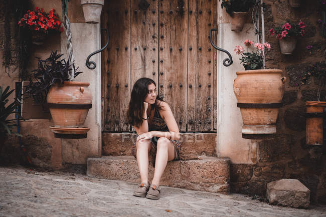 Young woman sitting near old building with flowers — Stock Photo