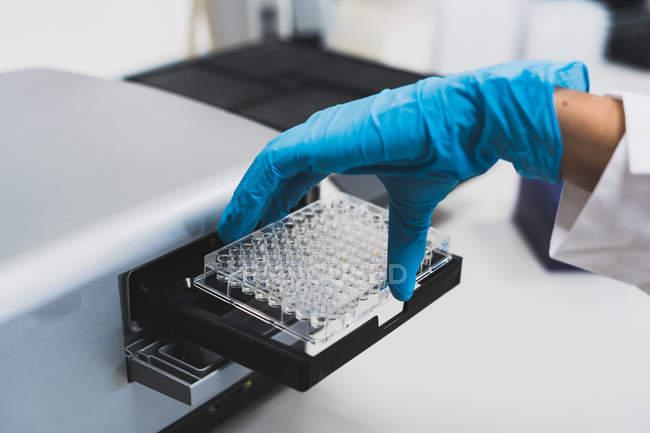 Рука исследователя в синей резиновой перчатке с использованием медицинского оборудования для проведения тестов в лаборатории — стоковое фото