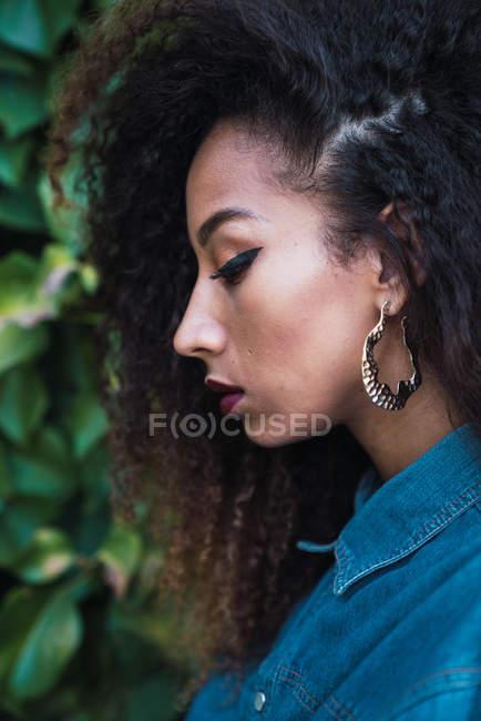 Pensativo afro-americano mulher de pé contra arbusto verde — Fotografia de Stock