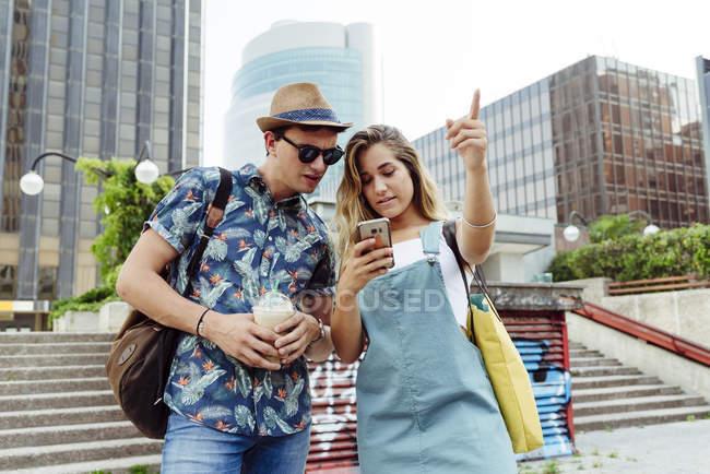 Пара переглядає смартфон на вулиці. — стокове фото