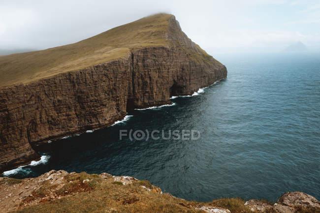 Oceano e scogliera rocciosa sotto il cielo nuvoloso sulle isole Feroe — Foto stock