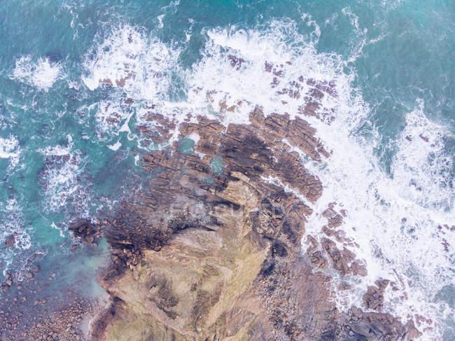 Удивительный вид на морскую воду, плещущуюся рядом с длинной скальной скалой в пасмурный день в Астурии, Испания — стоковое фото