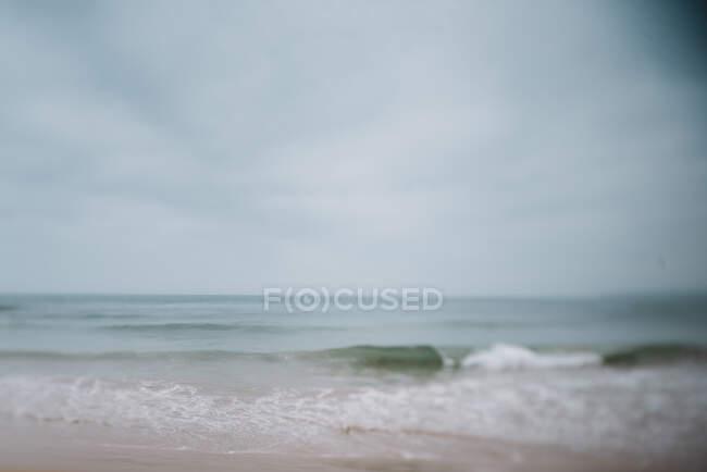 Вид на мыс с небольшими волнами в пасмурный день. — стоковое фото
