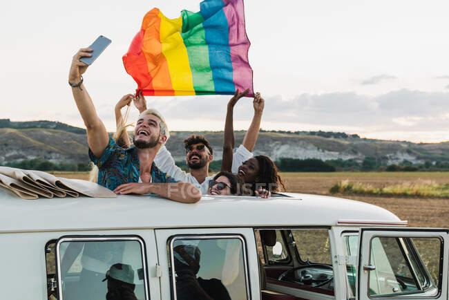 Persone con bandiera LGBT in furgone scattare selfie — Foto stock