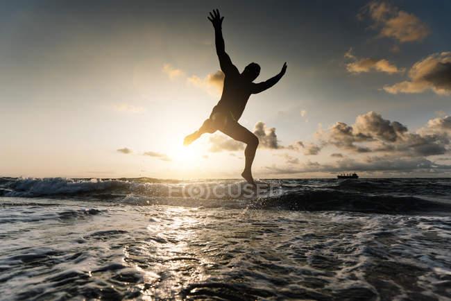 Silhueta de homem pulando na praia — Fotografia de Stock